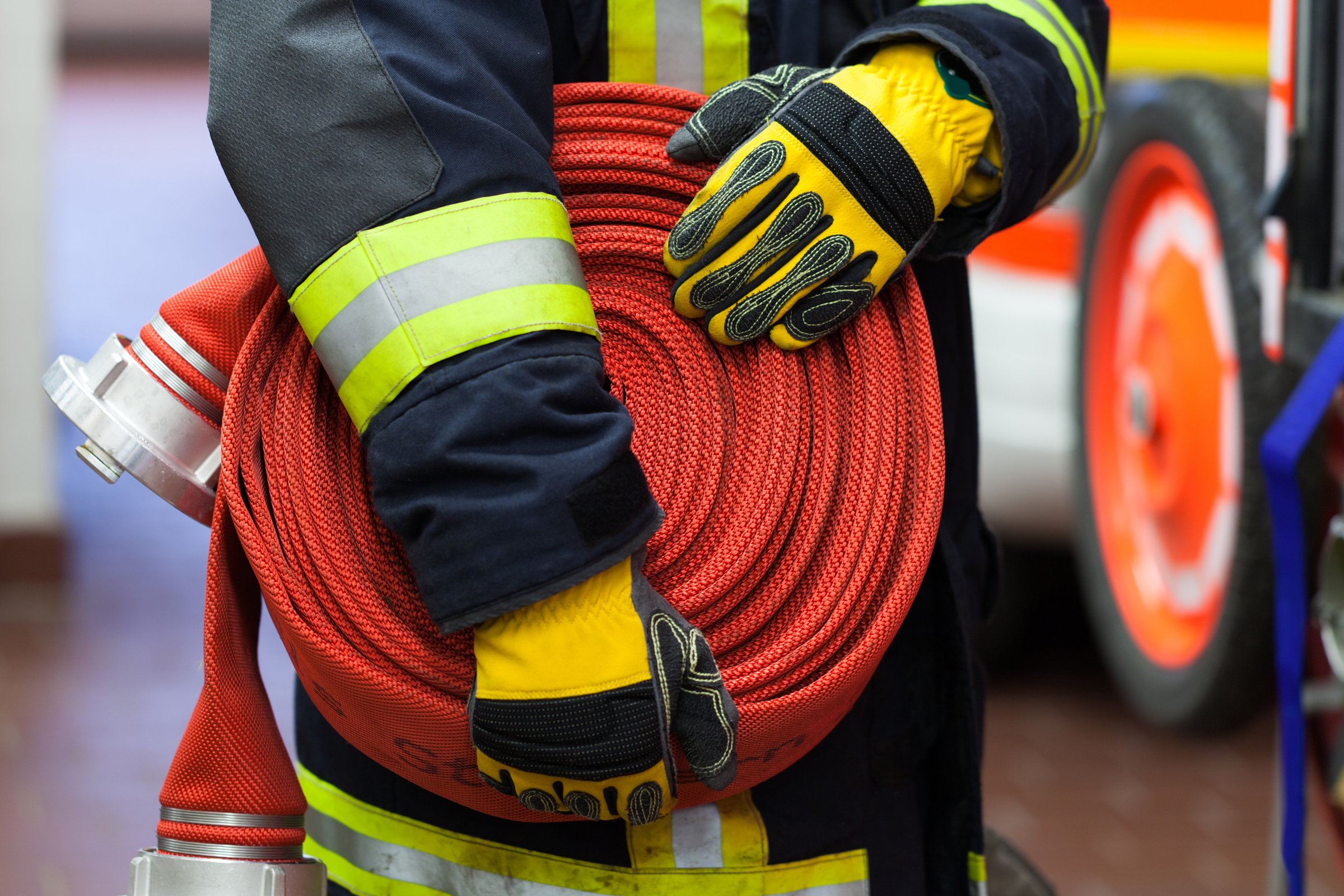 Firefighter Wearing A Rolled Hose