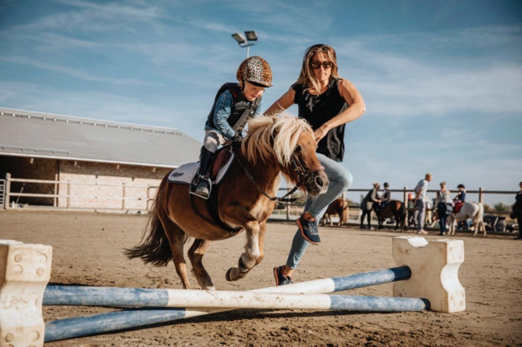 """Bilden togs i samband med ett uppdrag som jag gjorde för tidningen Häst&Ryttare i höstas. Det handlade om ett besök på Klagshamns Ridskola utanför Malmö. Den ridskolan liksom många andra ridskolor har hittat en ny grupp ryttare i så kallade """"minisar"""". Ryttare som börjar rida redan i 4-5 års åldern. Bilden föreställer Dion Engelbert som hoppar ett litet hinder med ponnyn Walle medan mamma Suzanne som hjälper till får hänga med."""